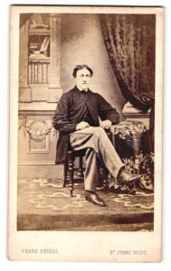 Fotografie Frank Briggs, St. Johns Wood, Mann im Anzug mit überschlagenen Beinen sitzend