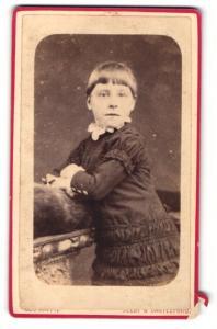 Fotografie George Nappy, Castleford, Mädchen im Kleid mit kurzen Haaren auf Tisch gelehnt