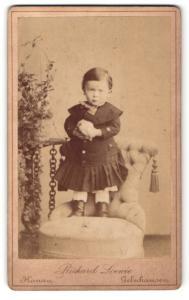 Fotografie Richard Leonie, Gelnhausen, kleines Mädchen in dunklem Kleid auf Sessel stehend