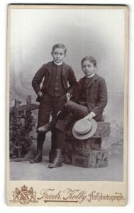 Fotografie Friedr. Kolby, Zwickau, Junge stehend im Anzug und Junge sitzend im Anzug mit Hut in der Hand