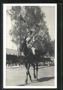 Foto-AK britischer Soldat zu Pferd durch den Ort reitend