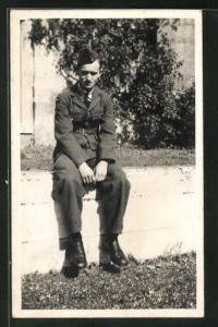 Foto-AK junger Soldat in britischer Uniform sitzt auf einer Mauer
