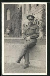 Foto-AK britischer Soldat in Uniform sitzt auf einer Mauer