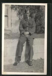 Foto-AK stattlicher Soldat in britischer Uniform auf einer Mauer sitzend