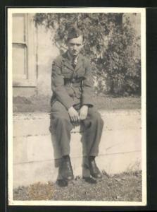 Foto-AK junger britischer Soldat sitzt in Uniform auf einer Mauer