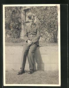 Foto-AK junger lächelnder Soldat in britischer Uniform auf einer Mauer sitzend