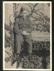 Foto-AK britischer junger Soldat in Uniform auf Mauer sitzend