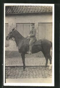 Foto-AK britischer Soldat zu Pferd in der Ortschaft unterwegs