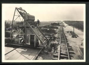AK Strassenbau, grosse Baumaschine auf Gleisen beim Bau an einem Damm der Autobahn