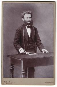 Fotografie Wilh. Krause, Jüterbog, Portrait Schneider mit Stoffschere und Massband