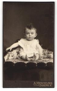 Fotografie A. Merckling, Zabern E., Kleiner Junge in weissen Klamotten auf Kissen
