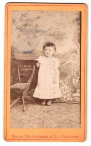Fotografie Mainberger & Fils, Wasselone, Kleines Mädchen in weissem Kleid hält sich an Stuhl fest