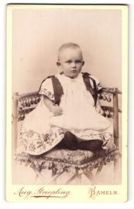 Fotografie Aug. Striepling, Hameln, Kleinkind in weissem Kleid auf Stuhl sitzend