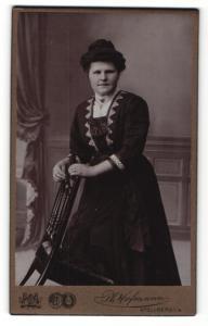 Fotografie Ph. Hoffmann, Stollberg i/S. , Frau mit hochgesteckten Haaren kniet mit einem Bein auf gekipptem Stuhl