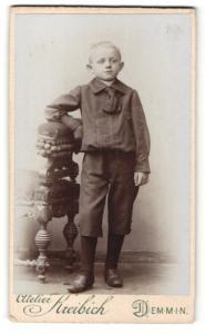Fotografie Atelier Kreibich, Demmin, Junge mit dicker halber Krawatte mit Arm auf Stuhllehne gestützt