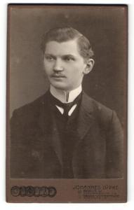 Fotografie Johannes Lüpke, Berlin, Mann im Anzug mit dünnem Binder und schmalem Oberlippenbart