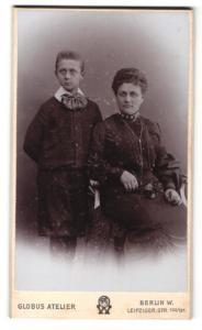 Fotografie Atelier Globus, Berlin, Frau im Kleid sitzend und Junge mit breiter Schleife am Hals stehend