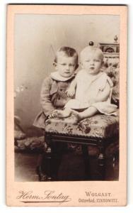 Fotografie Herm. Sontag, Wolgast, Kleinkind auf Sessel sitzend und Kind im Kleidchen daneben stehend