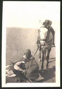 Fotografie Beduine mit Gewehr & Pferd macht Rast in der Wüste