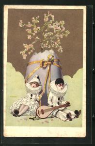 AK Art Deco, Harlekin Mädchen und Junge sitzen vor Ei mit blühendem Baum, goldene Farbe
