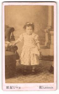 Fotografie H. Lutz, Kulmbach, Mädchen im Kleid stehend am Sessel festgehalten