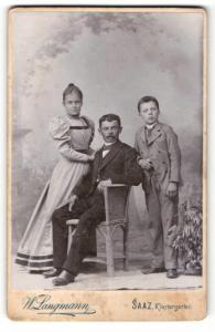 Fotografie W. Langmann, Saaz, Mann im Anzug sitzend und deneben Junge im Anzug und Mädchen im Kleid