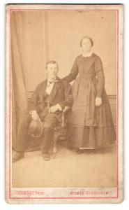 Fotografie Chambay, Paris, Mann im Anzug mit Hut sitzend und Frau im Kleid stehend