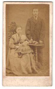 Fotografie F. Cole, London, Mann mit Kotletten im Anzug stehend und Frau im Kleid sitzend mit Baby auf den Armen