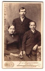 Fotografie J. v. Szymononricz, Graudenz, Frau im Kleid sitzend und Mann und Junge in Anzügen stehend