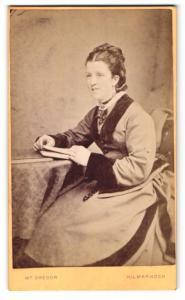 Fotografie M. Gregor, Kilmarnock, Frau im Kleid am Tisch sitzend mit Buch in den Händen