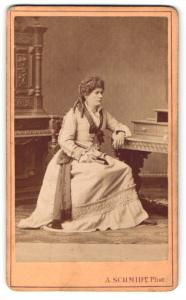 Fotografie A. Schmidt, Pforzheim, Frau im Kleid sitzend an Tisch gelehnt mit eingedrehten Haaren