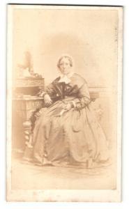 Fotografie C. Höpfner, Halle a / S., Portrait Dame mit Haube u. Buch am Schreibtisch sitzend