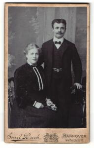 Fotografie Emil Buch, Hannover, Portrait bürgerliches Paar in eleganter Kleidung mit Blume