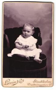 Fotografie Leverin & Co., Stockholm, Kleinkind im Kleidchen auf Sessel sitzend