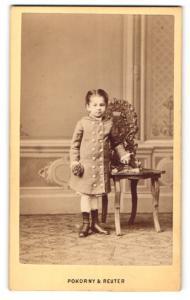 Fotografie Pokorny & Reuter, Wien, kleines Mädchen im Mantel mit Blume in der Hand neben Stuhl stehend