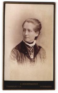 Fotografie E. Rheinstaedter, Wiesbaden, Frau im Kleid mit dicker Halskette und Amulett