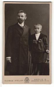 Fotografie Atelier Globus, Berlin, Mann im Anzug mit Jungen im Anzug mit Schleife am Bauch