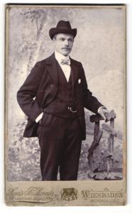 Fotografie Louis Frohrvein, Wiesbaden, Mann im Anzug mit Hut und Fliege stehend