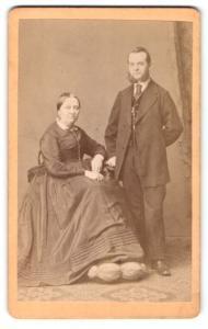 Fotografie Wilhelm Grundner, Berlin, Mann im Anzug mit Backenbart und Frau im Kleid sitzend