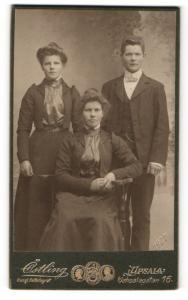 Fotografie Olof Östling, Upsala, Zwei Frauen in Kleidern eine stehend eine sitzend und ein junger Mann im Anzug stehend