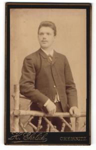 Fotografie H. Ehrlich, Chemnitz, Mann im Anzug stehend auf Holzzaun gestützt
