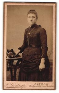 Fotografie J. Göstrup, Altona, Frau im Kleid stehend mit Halskette und Amulett daran