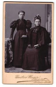Fotografie Gustav Unger, Forst n/L., Frau im Kleid mit Puffärmeln stehend und Frau im Kleid mit Umhang sitzend