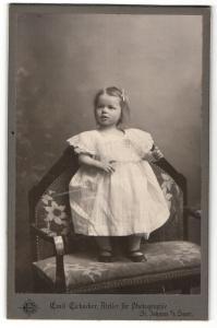 Fotografie Emil Eichacker, St. Johann / Saar, Mädchen im weissen Kleid auf Sessel stehend