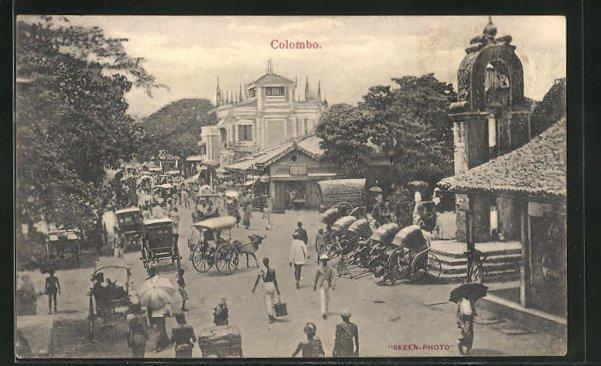 AK Colombo, Blick auf geschäftige Strasse mit Händler, Rikschas und Häuser 0