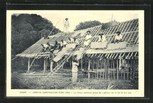 AK Samkitam construction d'une case, les Eleves catechistes posent des pailles sur le toit de leur case
