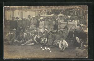AK Gruppenportrait von Damen und Herren in Bademode vor einem Geschäft am Strand