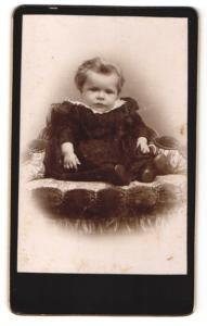 Fotografie unbekannter Fotograf und Ort, Kleinkind in dunklem Kleidchen auf Sessel sitzend