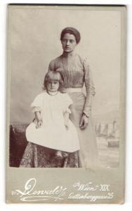 Fotografie v. Renwald, Wien, Frau im Kleid stehend mit kleinem Mädchen im Kleid