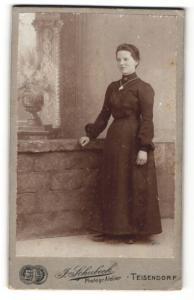 Fotografie J. Schubeck, Teisendorf, Frau im Kleid mit Halskette und Amulett mit Arm auf Wand gestützt